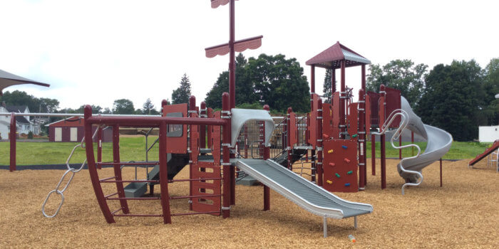 Photo of play structure shaped like a ship, with slides, climbing components, a ship's wheel, and a custom mast.