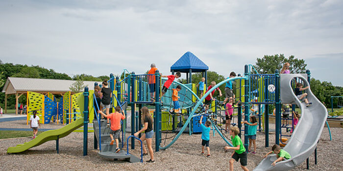 Photo of playground with slides, climbers, bridges, and butterfly shaped climbing walls.