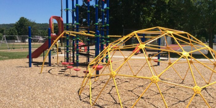 Photo of a playground with climbing structures and a slide.