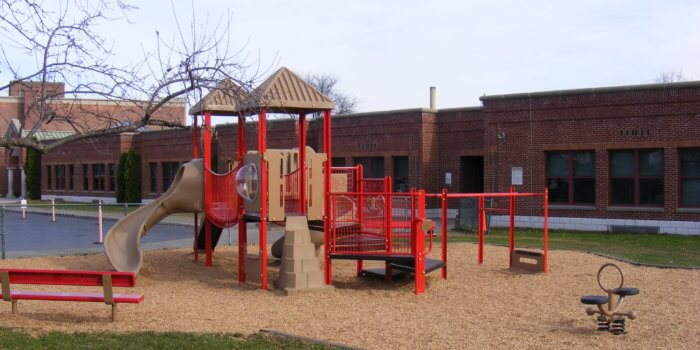 Photo of playground with bridge, climbers, slides, and independent play components.