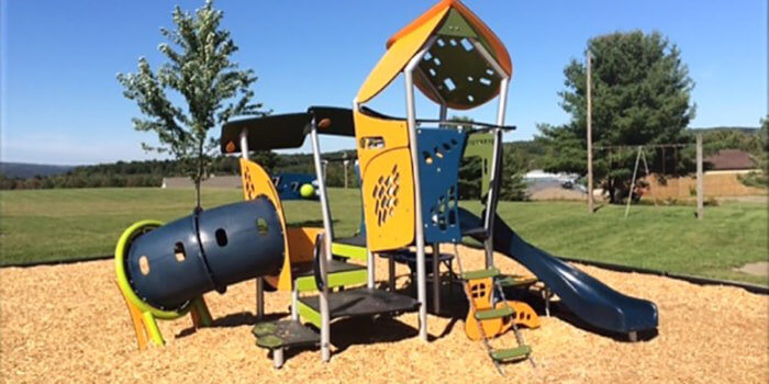 Photo of small play structure with slide, climbers, play panels, and a tunnel.