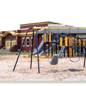 Photo of playground with swings, climbers, slides, and a large spinner.