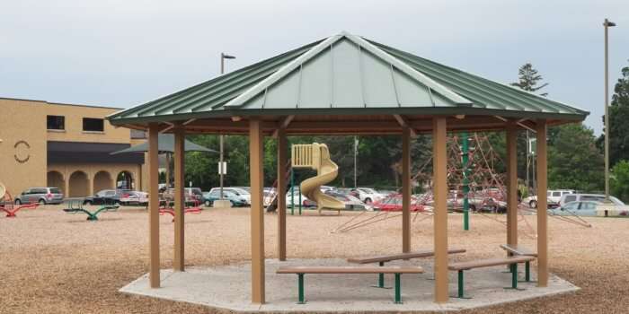Photo of open air shelter with benches and play equipment in the background.