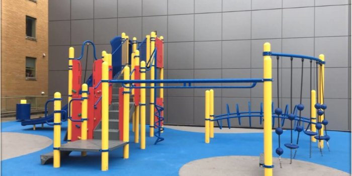 Photo of playground with climbers, slides, and poured-in-place rubber surfacing.