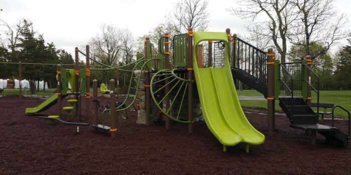 Photo of play structure with multiple decks, climbers, slides, and swings