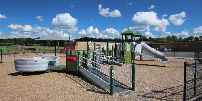 Photo of playground with swings, climbing nets, spinners, and a main play structue with slides, climbers, and ramps.