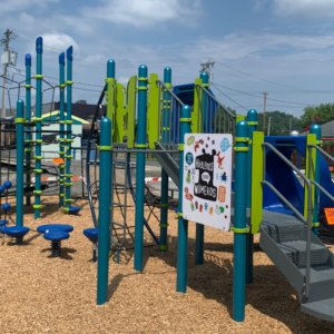 Photo of playground with slides, climbers, play panels, and climbing net tower.