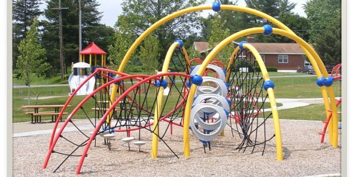 Photo of playground with curved climbing nets, ladders, and slides.