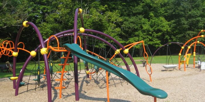 Photo of a playground with curved climbing structures and a slide.