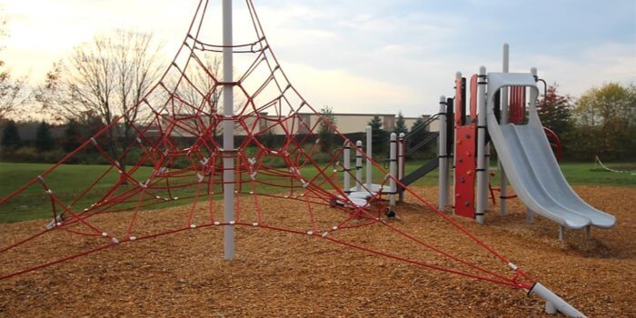 Photo of rope climbing structure and play structure with climbers and slide.