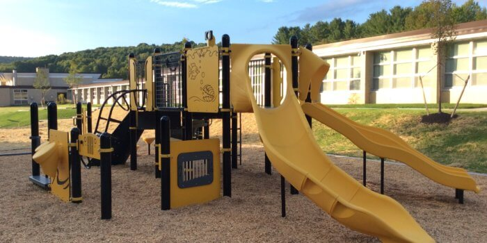 Photo of play structure with multiple slides, climbers, and play panels.