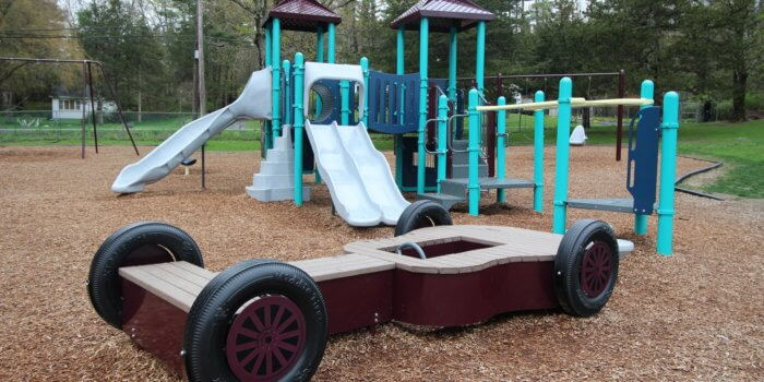 Photo of playground with slides, climbers, and a custom guitar dragster.
