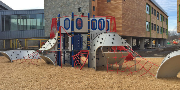 Photo of a modern ship inspired play structure, with futuristic metal climbing panels and numerous other play components